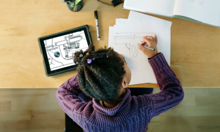 child copying drawing from a tablet device to paper
