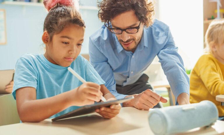 child works on tablet device as adult facilitator observes