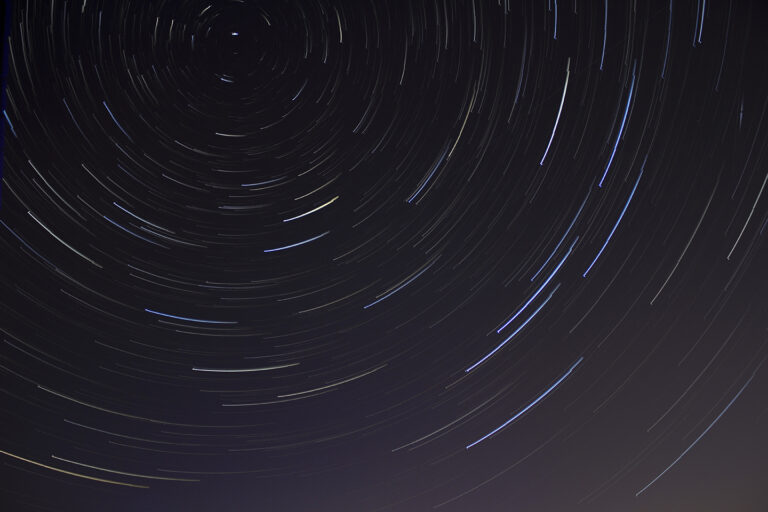 time lapse image of black sky with stars blurring in circular motions